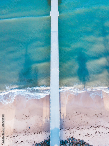 Aerial view of long jetty towards the ocean.
