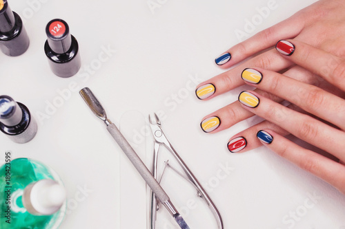 Deurstickers Manicure Creative nail design multicolored manicure with red yellow blue black color. Hands close-up with tool on white background.
