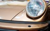 Goldener Sportwagen mit rundem Schweinwerfer