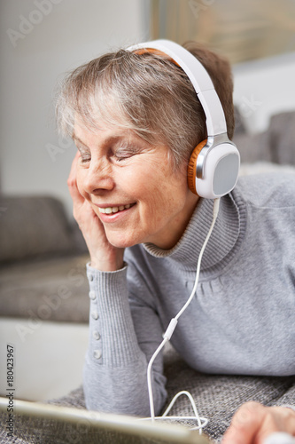 Fotobehang Muziek Seniorin hört mit Genuss Musik über Kopfhörer