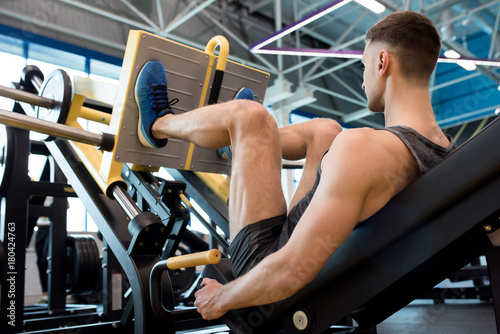 Sticker Rear view of muscular sportsman doing leg exercises using machine in modern gym