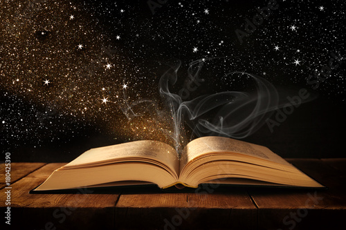 image of open antique book on wooden table with glitter overlay. - 180425390