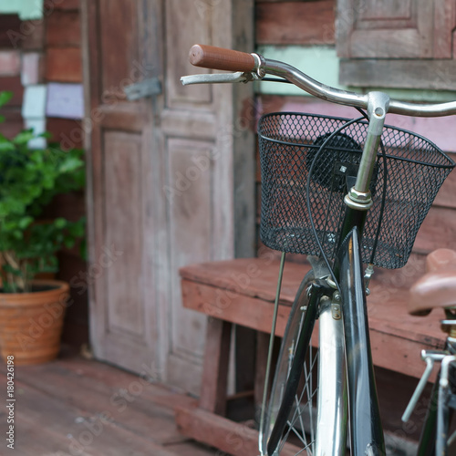 Fotobehang Fiets go home with blue vintage old black and brown bicycle or bike at front of retro wooden home terrace with wood door and window with tree in flowerpot for exterior and interior decor or background