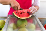 Women in red apron, latex glove cut watermelon with knife. Asia. Thailand. Fresh fruit