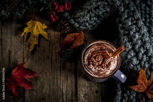 Poster Autumn drinks, hot chocolate or cocoa with whipped cream and spices (cinnamon, anise), on the old rustic wooden table, with a warm cozy blanket, hay berry and leaves copy space top view