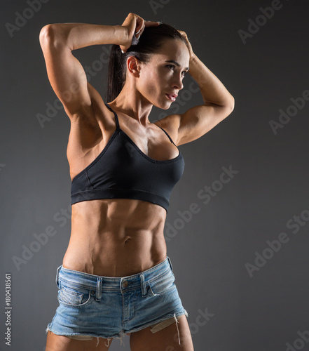 Wall mural  athletic young woman with muscles doing exercises with dumbbells bodybuilding in the gym