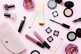 Fototapety Female beauty items on pastel background. Pink purse, make up products, flowers.