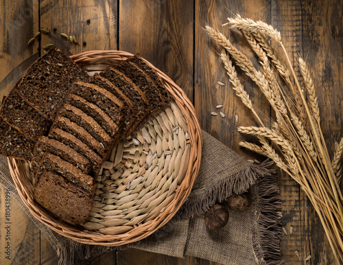 Fototapeta Sliced rye bread in a wicker tray and spikelets on wooden surface