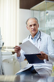 Senior practitioner in uniform looking through medical papers in clinics - 180439543