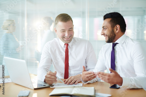 Two happy men in formalwear discussing new ideas and preparing report for seminar or conference in office