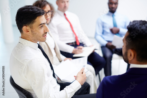 Young confident employee talking to one of co-workers during business gathering