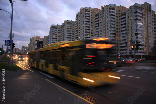 The motion of a blurred bus on the street at dusk Poster