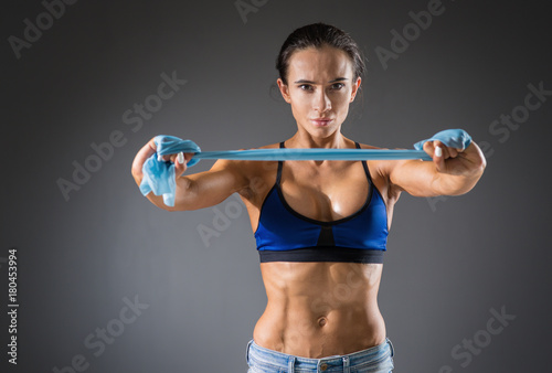 Poster athletic young woman with muscles doing exercises with dumbbells bodybuilding in the gym