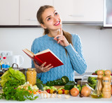 Girl with book of recipes at kitchen - 180457167