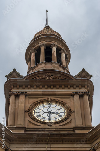 Fotobehang Sydney Sydney, Australia - March 25, 2017: Closeup of top of brown stone Town Hall Clock Tower. White and gold time piece. Against heavy gray sky.