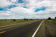 Straight wet road leading throught Arizonas beautiful prairie