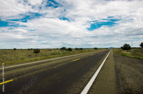 Papiers peints Arizona Straight wet road leading throught Arizonas beautiful prairie