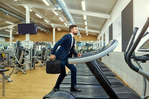 A businessman is running on a treadmill in the gym.