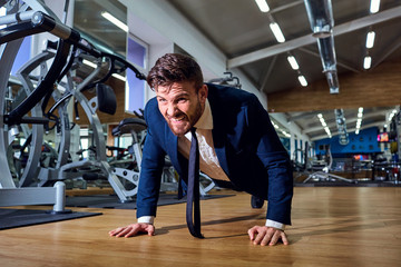 Businessman doing push-ups from the floor in the gym.