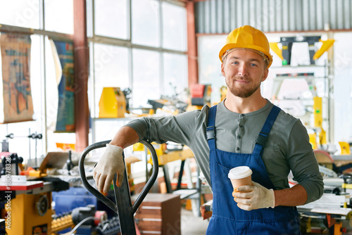 Portrait of young worker taking break in factory workshop looking at camera holding coffee cup and smiling happily