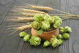 Beer brewing ingredients Hop cones in wooden bowl and wheat ears on dark wooden background. Beer brewery concept. Beer background - 180484185