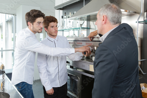 Papiers peints Cafe Waiters learning how to use coffee machine