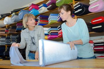 beautiful brunette choosing fabric skeins in textile shop