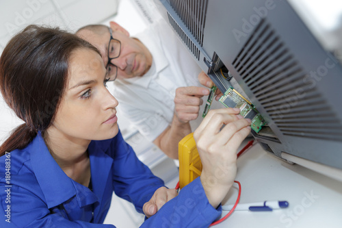 young woman checking multimeter - 180488367