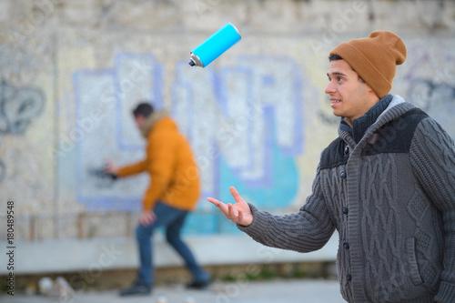 Fotobehang Graffiti graffiti artist playing with spraying can