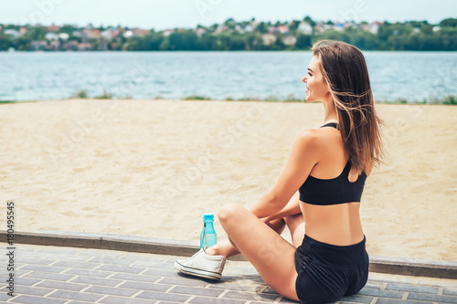 Cute sporty girl relaxing outdoor after training