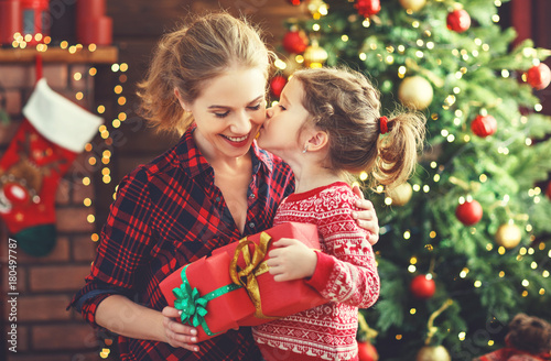 Leinwandbild Motiv happy family mother and daughter giving christmas gift