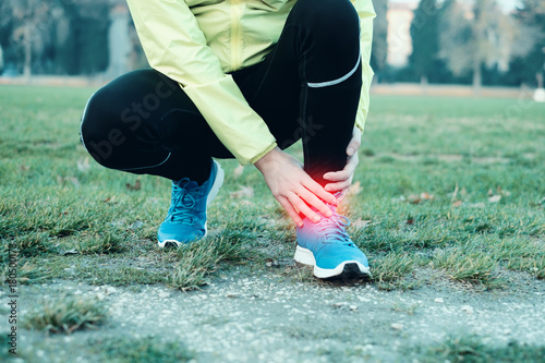 Poster Runner with injured ankle while training in the city park in cold weather