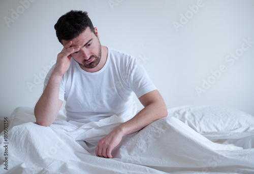Sad and upset man waking up in the morning