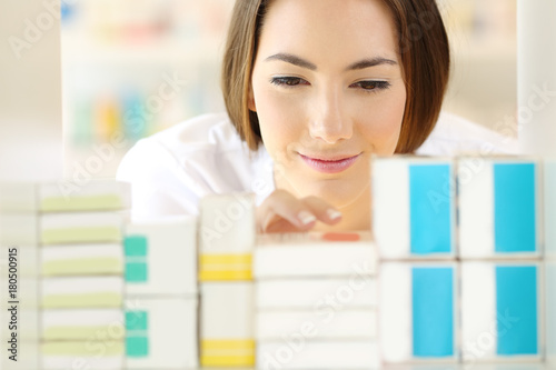 Plexiglas Apotheek Relaxed pharmacist searching medicines in a pharmacy