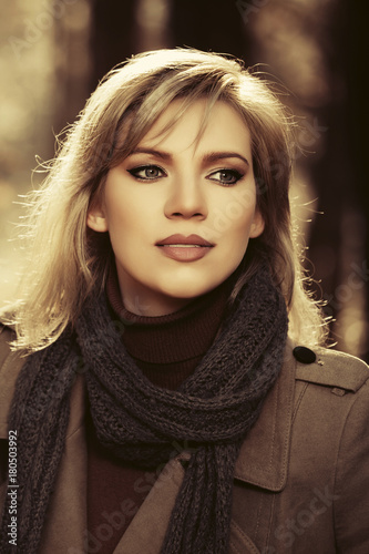 Plakat Young fashion woman in classic beige coat walking in autumn forest