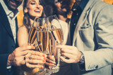 Men and women celebrating birthday or new years party while clinking glasses with sparkling wine - 180506305
