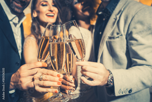 Foto Murales Men and women celebrating birthday or new years party while clinking glasses with sparkling wine