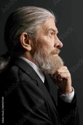 Pensive old male on dark background. Senior man portrait in profile in studio.