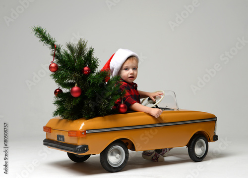 Small child boy in winter sitting in a yellow  retro toy car pulls on Christmas tree decorated
