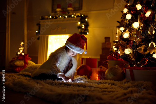 Cute little girl sitting near Christmas tree and fireplace and using tablet.