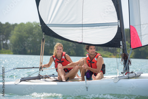 a couple sitting on a sail boat