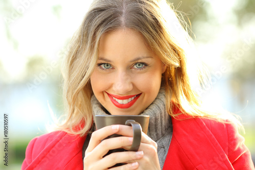 Poster Woman looking at you holding a cup of coffee in winter