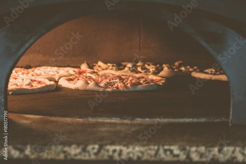 Foto op Plexiglas Pizzeria sfondo con pizze su forno a legna