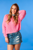 Beautiful funky woman in pink sweater and jeans skirt dance over blue background