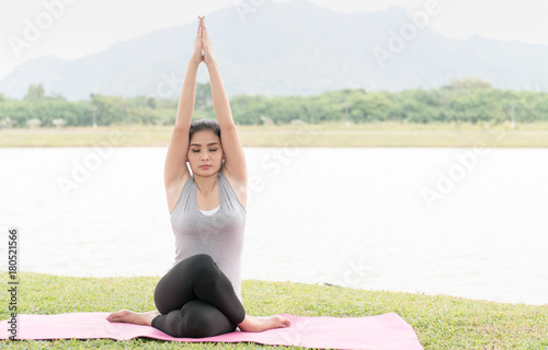 Wall mural young woman exercising and sitting in yoga position