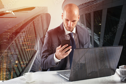 Businessman works with smartphone and laptop