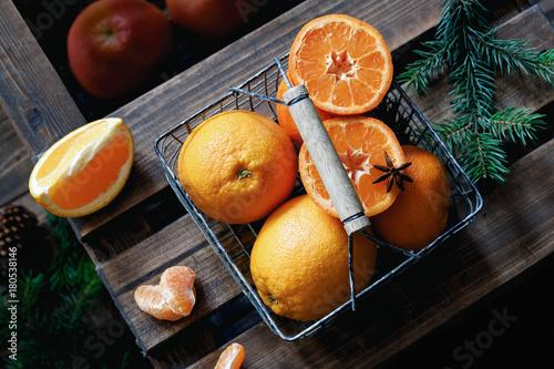 Oranges in basket on wooden background. Tangerines, oranges, mandarines for Christmas