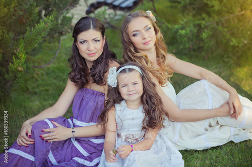 Foto op Canvas Rotterdam Stunning Brunette blond chestnut blue eyes sisters girls wearing stylish white purple dress enjoying life time together summer sunny day in garden forest on green grass happy smiling