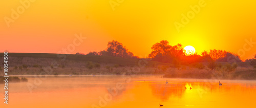 Aluminium Oranje foggy, colorful sunrise over the lake
