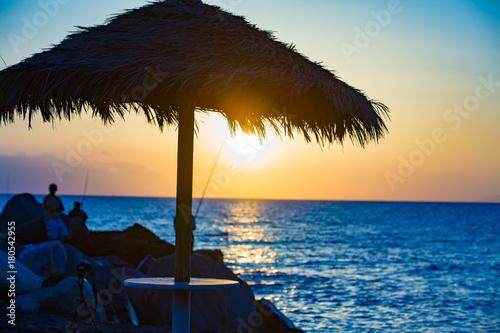 Aluminium Strand Beach umbrella and sun beds on the sea beach at sunset